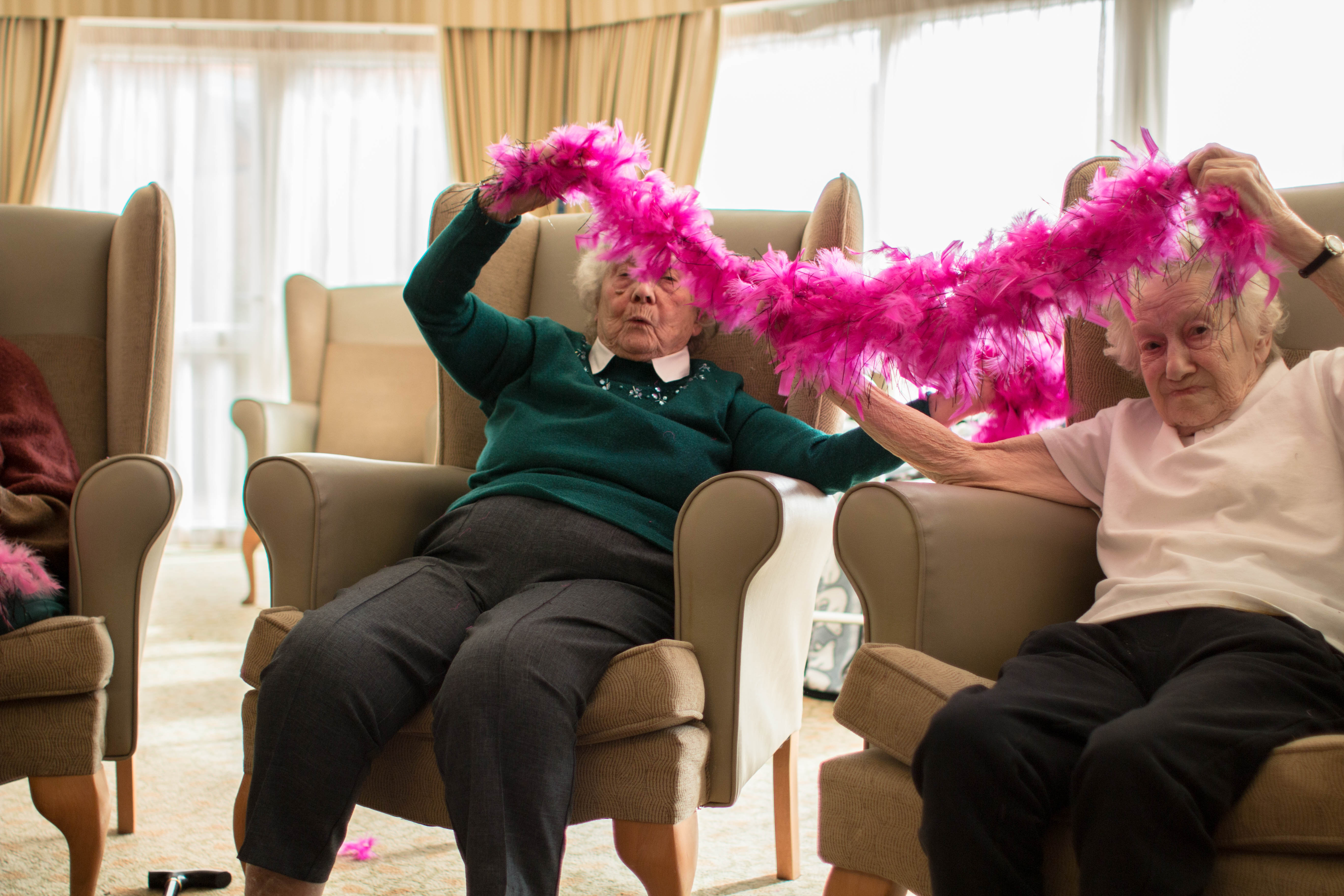 Craig Healthcare West Farm Care Home armchair aerobics ladies having fun with feathers